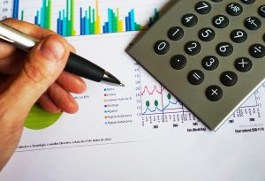 Hand holding pen with calculator